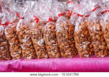 A line- up of neatly packaged peanut snacks in transparent bags on top a table.