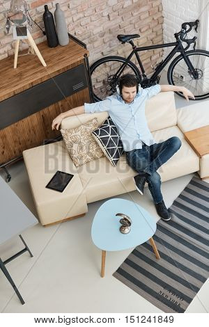 Young man sitting on sofa, listening to music through headphones, relaxing.