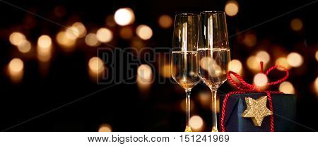 Christmas present with champagne glasses in front of a festive lighted background