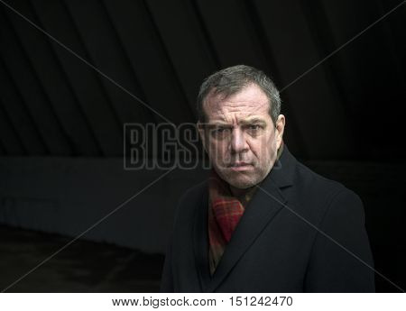 Gloomy frustrated middle-aged man in a black coat
