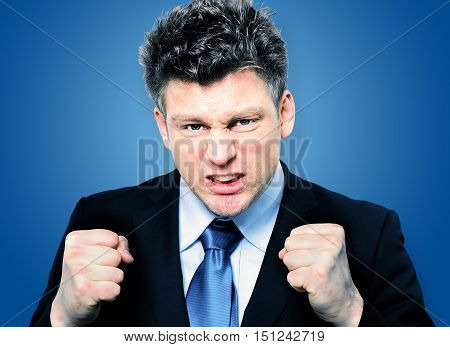 Closeup portrait of handsome businessman clenching fists to motivate team in office