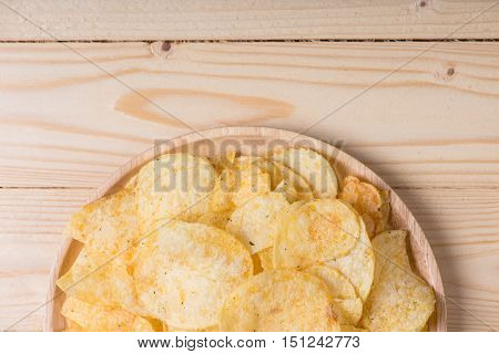 potato chips on wooden table. potato chips background.