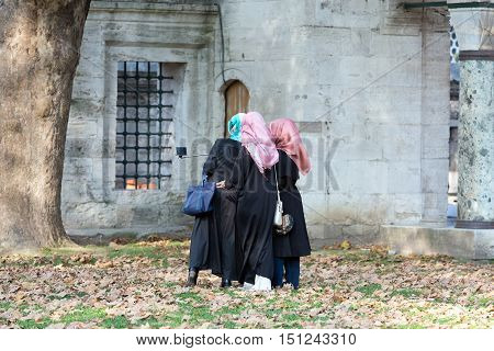Group of Three Islamic dressed Ladies making self Portrait Photo at Park of historical Mosque using stick for Mobile Telephone Camera. Istanbul, Turkey, November 19, 2015
