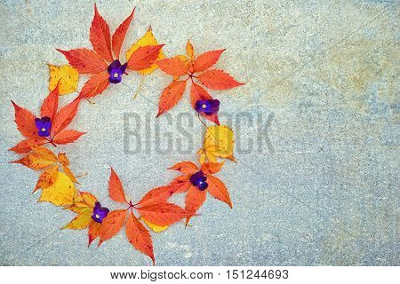 A Wreath Of Autumn Birch And Grape Leaves And Pansies On A Neutral Gray Background With Copy Space F