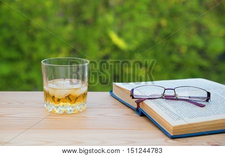 Glass of whiskey on table with books and spectacles