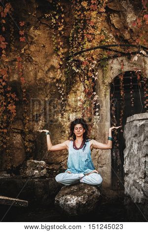 young woman practice yoga on rock outdoor in front old wall and cliff autumn day