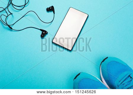 Black headphones, smart phone and blue sneakers on blue background. Concept of active lifestyle.