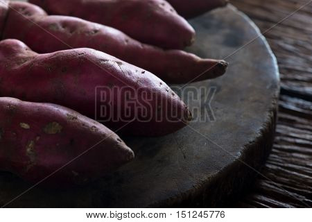 Raw sweet potatoes on wooden background. Sweet potatoes on dark tone. Sweet potatoes.