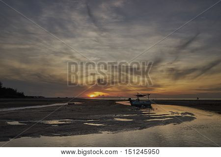 fishing boat at low tide greeting the morning sun