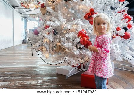 Portrait Of Little Girl In A Pink Shirt Standing By Christmas Tree
