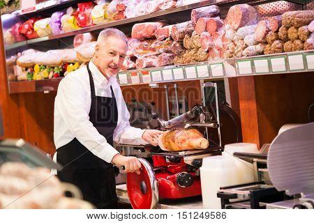 Shopkeeper cutting ham in a grocery store
