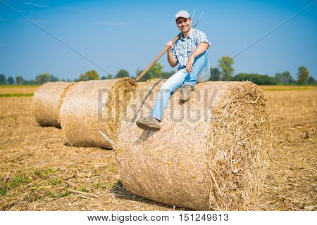 Portrait of a smiling farmer sitting on an hay bale in his field