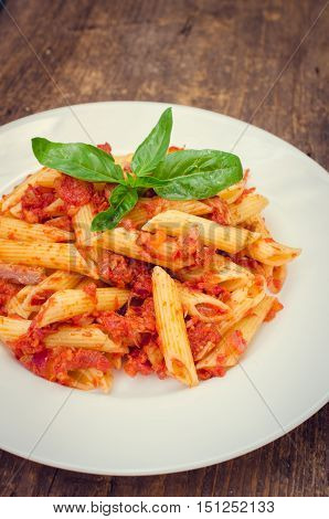 Italian Wholemeal Pasta Penne with Tuna and Basil. Fresh pasta with tuna and tomato sauce on old wooden background with place for text. Italian cuisine concept. Copy space. Selective focus.