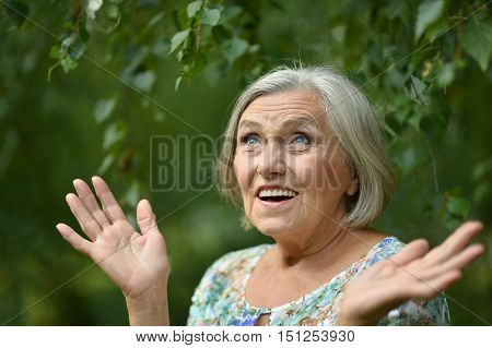 Portrait of a surprised senior woman in summer park