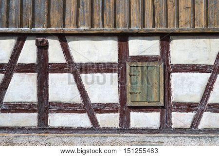 Old half-timbered facade with a closed window shutter