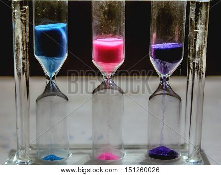 hourglass in three different colors closeup standing on the table