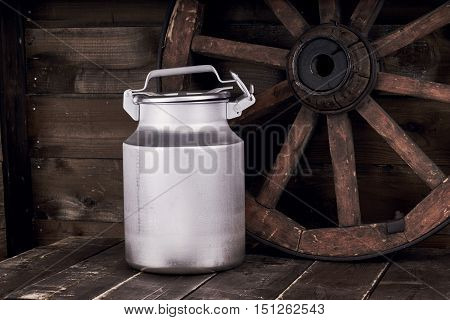 Aluminium water can standing on grunge wooden tabletop or floor near old wheel against wood wall background