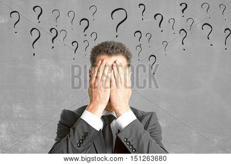 Young businessman covering face with palms on concrete background with question mark sketches. Failure and fear concept