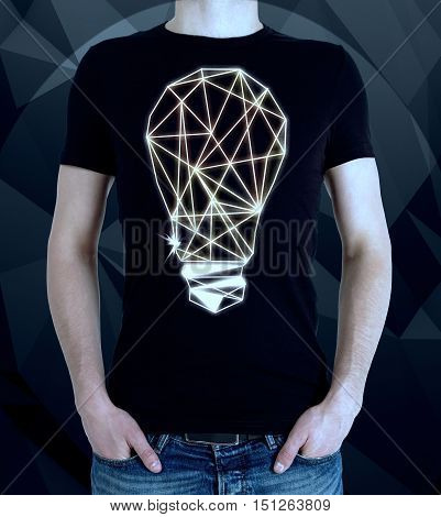 Young man wearing t-shirt with creative polygonal light bulb on dark background. Idea concept