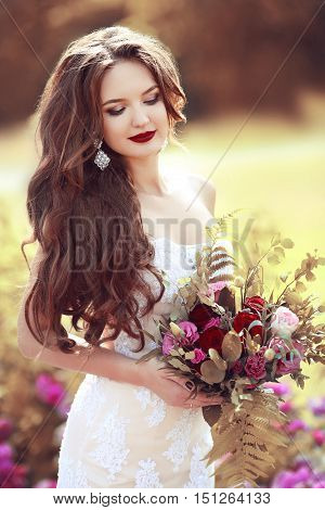 Wedding Portrait Of Beautiful Brunette Bride With Long Wavy Hair Holding Bouquet Of Rose Flowers Pos