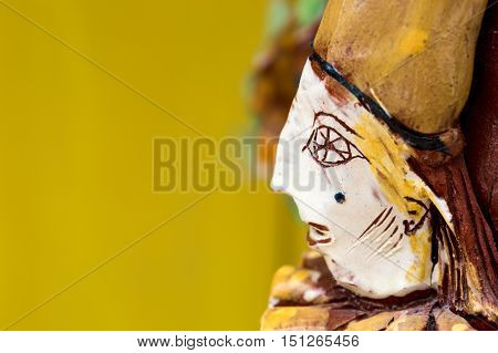 Close up of a jesters face made in glazed ceramics. Yellow background. Copy space.
