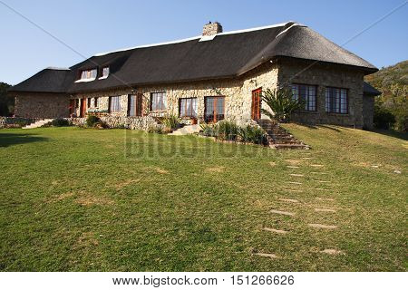 Large stone house with a thatched roof in the mountains used for hunting