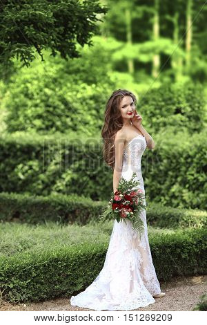 Wedding Portrait Of Beautiful Bride With Long Wavy Hair Wearing In White Lace Wedding Dress Holding
