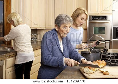 Elderly Woman Cooking with her daughter in the kitchen. She is cutting bread.  Another younger woman is in the background at the sink.
