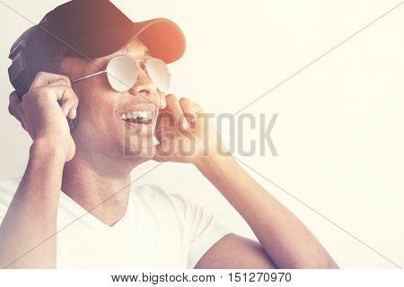 Portrait of happy african american man in cap and glasses listening to music with headphones on light background. Toned image