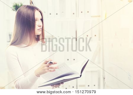 Woman With Book Looking At Business Charts