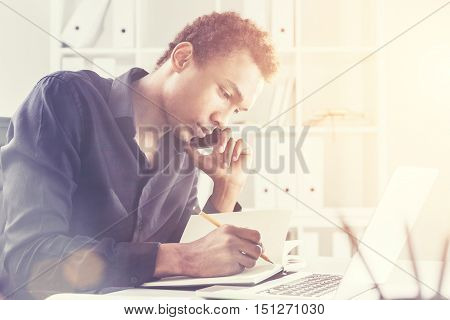 Concentrated Black Man On Phone With Pencil