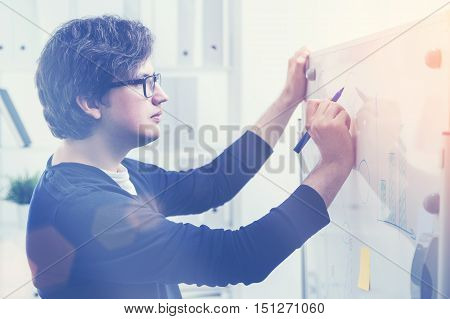 Side view of attractive european man drawing business charts on office whiteboard. Toned image