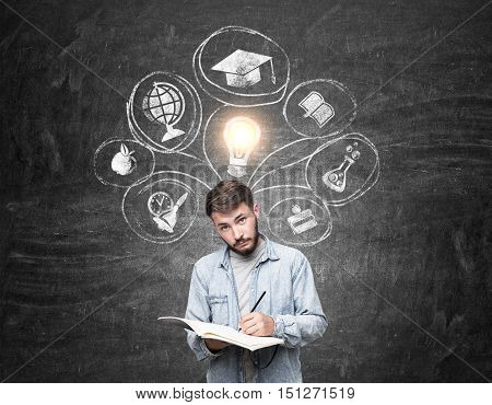 Portrait of man writing in his notebook and standing near blackboard with education sketches on it. Concept of studying opportunities