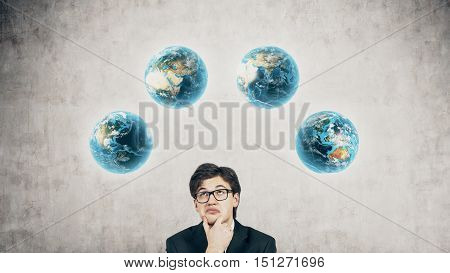 Guy full of doubts standing near bow of planets Earth against concrete wall. Concept of seeing the world.