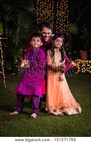 Father and kids playing with firecrackers or fire crackers or phuljhadi or fulzadi on diwali night