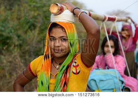 PALITANA GUJARAT INDIA - JANUARY 25: Indian woman which on the head is transporting pilgrims to the holy Palitana top in the Gujarat state in India Palitana in January 25 2015