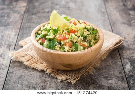 Tabbouleh salad with couscous in bowl on rustic table