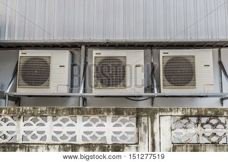 Air compressors hung on the outside wall of the building.