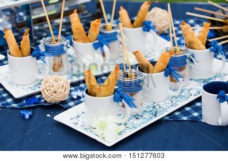 Pork satay and Fried spring rolls on a plate