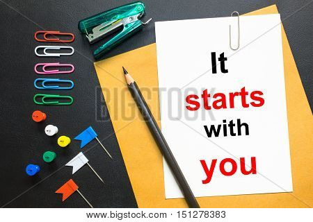 Word IT START WITH YOU! on white paper background
