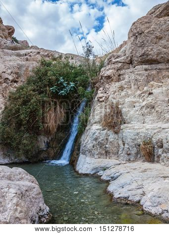 Adorable little waterfall among rocks parched desert. The journey through the national park Ein Gedi, Dead Sea, Israel