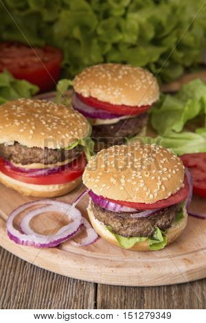 Mini burgers with the fresh vegetables on a wooden board
