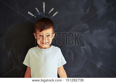 Smiling little boy is posing against blackboard with chalk drawing of exclamation marks