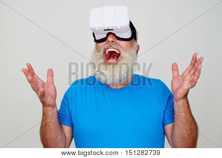 Smiling senior bearded male in blue T-shirt is impressed while testing 3D virtual reality technology with the help of VR-headset