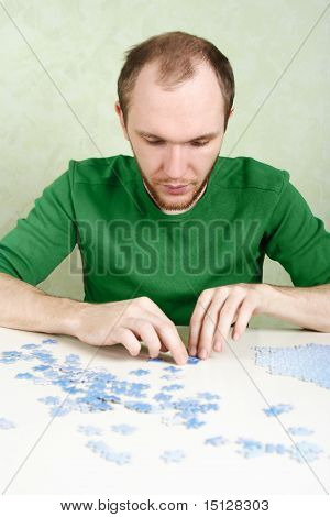 Man In Green Shirt Assembling Blue Puzzle Pieces
