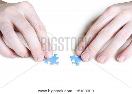 Closeup Of Mans Hands Assembling Two Blue Puzzle Pieces, Isolated