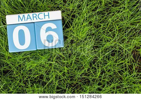 March 6th. Day 6 of month, wooden color calendar on football green grass background. Spring time, empty space for text.
