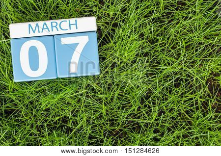 March 7th. Day 7 of month, calendar on football green grass background. Spring time, empty space for text.