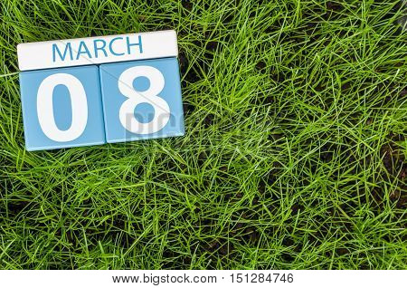 March 8th. Happy International Women's Days. Day 8 of month, calendar on football green grass background. Empty space for text.