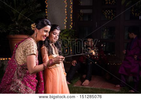 Indian mother and daughter playing with firecrackers or fire crackers or phuljhadi or fulzadi on diwali night